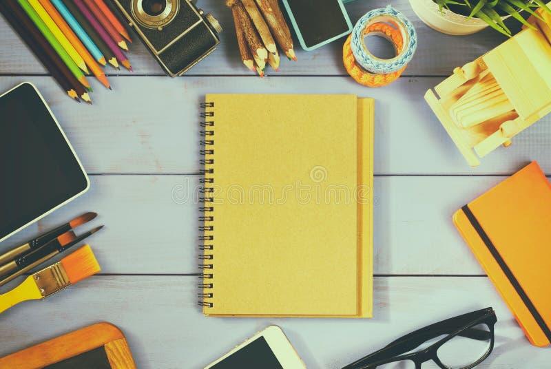 Draufsichtfoto des leeren Notizbuches, der alten Kamera und des Schulbedarfs stockfotografie