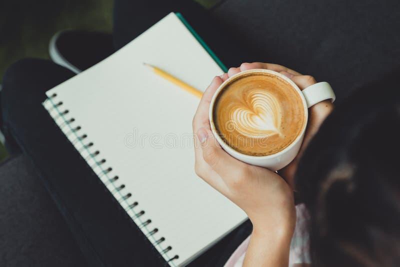 Draufsichtfrauenhand, die heiße CappuccinoKaffeetasse mit Herzen hält stockfoto