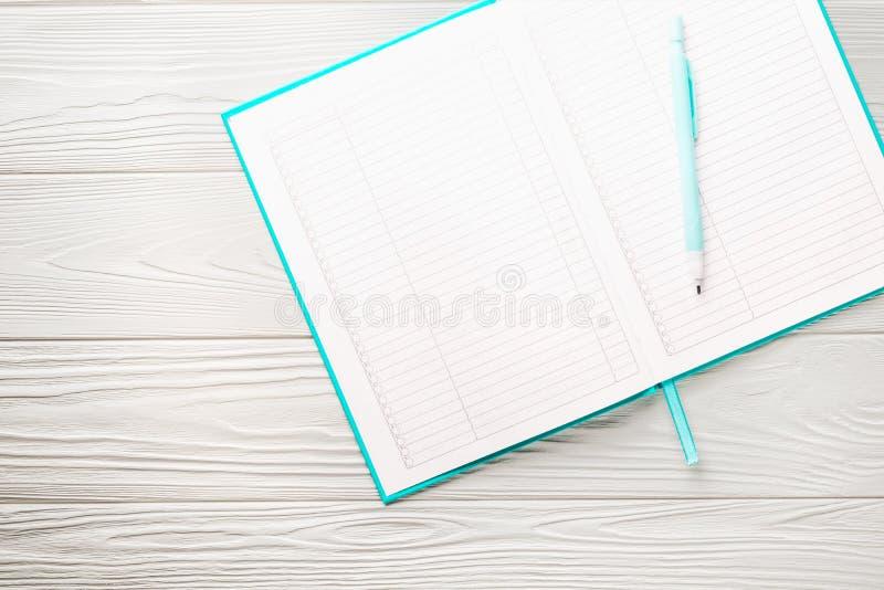 Draufsichtgrünabdeckungsnotizblock mit Bleistift auf weißem Holztisch stockfoto
