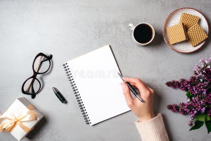 Draufsichthand der Frau Textnachricht auf Notizbuch des leeren Papiers auf Steintabelle schreibend Ebene gelegte lila Blume, weib stockfotografie