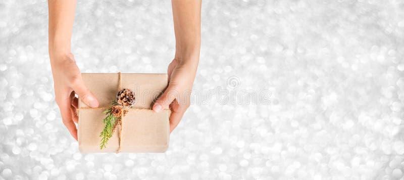 Draufsichthand, die Weihnachtspräsentkarton mit silbernem Schein bokeh hält stockfotos