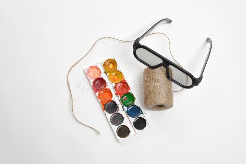 Draufsichtkunstszenenaufmachung der Threadschnur, der Gläser und der Aquarellfarben auf einem weißen Hintergrund stockbild