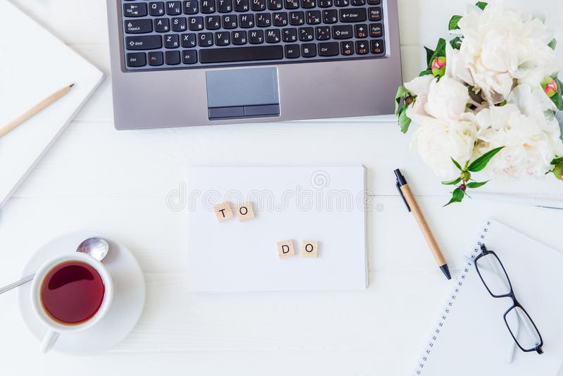Draufsichtlicht-Arbeitsplatz mit Laptoptastatur, Notizbuch mit, ZUM der Beschriftung, Tasse Tee ZU TUN, sletchbook, Gläser, weiße lizenzfreies stockbild
