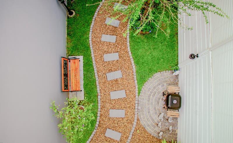 Draufsichtluftfoto vom Fliegenbrummen der Steingehwegwicklung im Garten lizenzfreie stockfotos