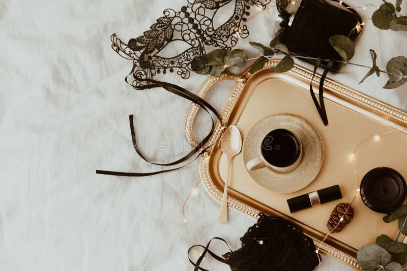 Draufsichtmodegold und schwarzes Zubehör Maske, Kaffee, Lippenstift und Spitzewäsche stockfotos