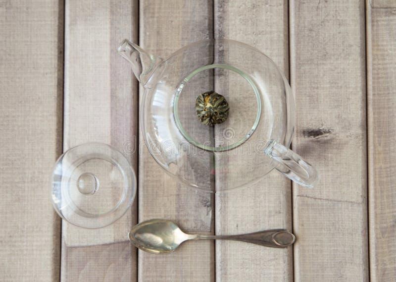 Draufsichtnahaufnahme eines Glasteetopfes mit dem chinesischen Tee der Blume bereit zu gebraut und eine Kappe auf hölzernem Hinte stockfotos