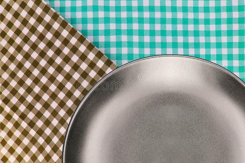 Draufsichtplatte auf kariertem Tischdeckenmusterhintergrund lizenzfreie stockfotos