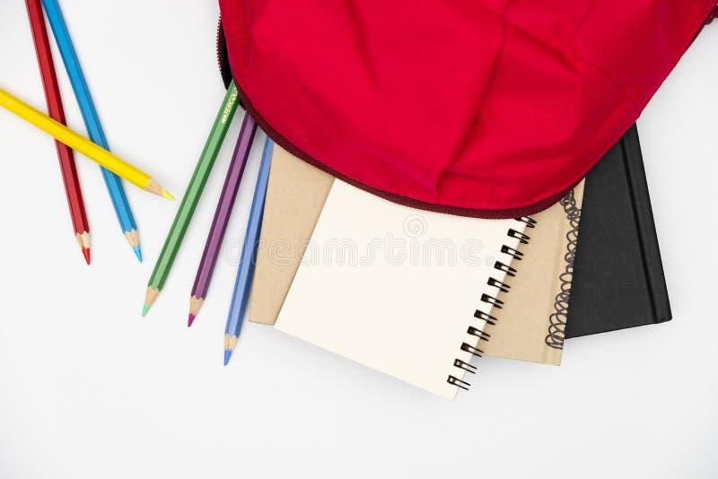 Draufsichtrucksack und Schulbriefpapier auf weißem Hintergrund lizenzfreies stockfoto