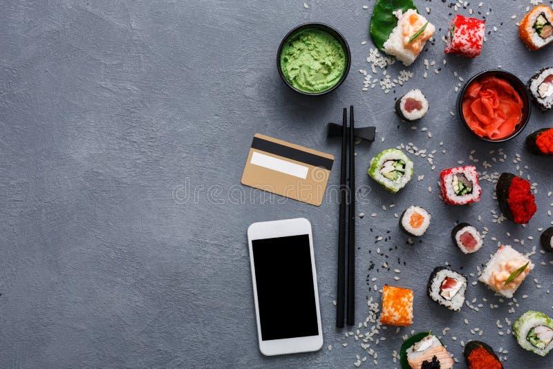 Draufsichtsatz der Sushirolle und des gunkan nahen Telefons und Kreditkarte auf rustikalem Grau- und Reishintergrund stockfotografie
