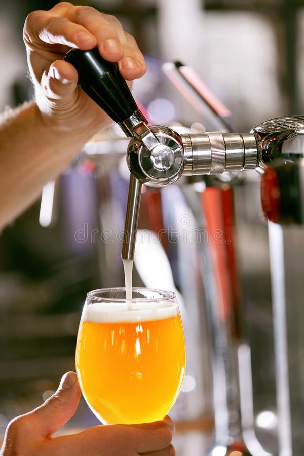 Draught Beer. Closeup Pouring Fresh Beer In Glass. Draught Beer. Closeup Pouring Fresh Wheat Beer In Glass From Beer Taps In Pub. High Resolution stock photography