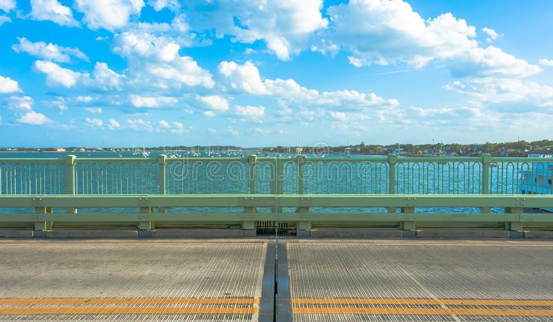 Draw Bridge. Overlooking the center of a old draw bridge shows where the road will split. and the railing. all in the bright daylight with blue sky and large stock image