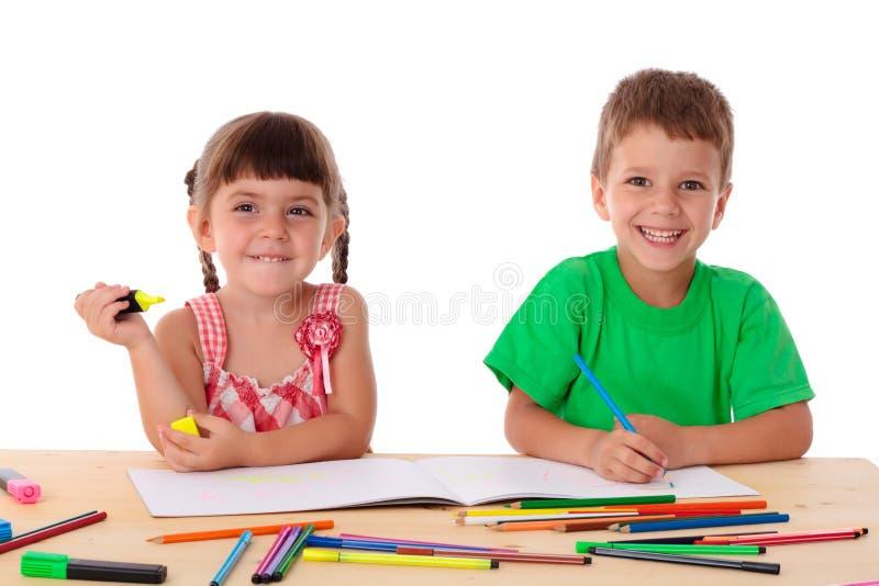 Draw för två liten ungar med crayons arkivbild