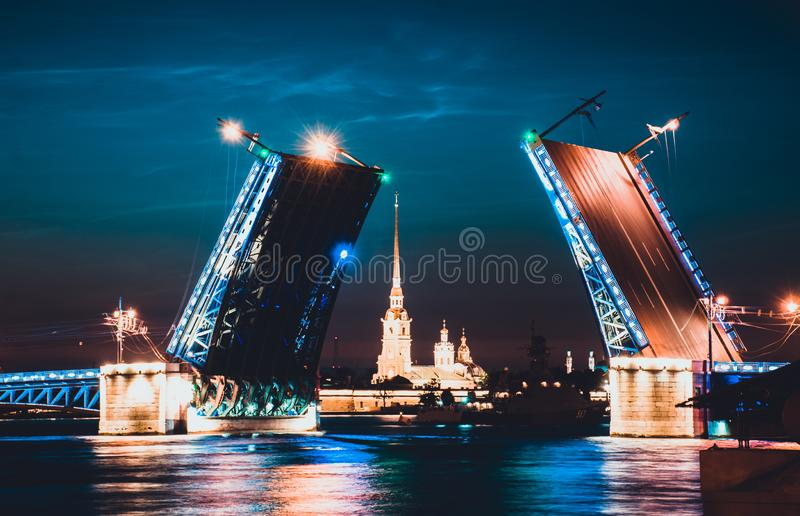 A drawbridge of Saint Petersburg at night and fortress between it. A drawbridge of Saint Petersburg at night with a fortress between it and lights reflected in royalty free stock images