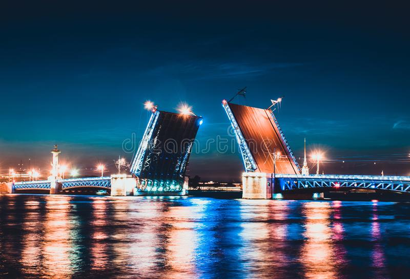 A drawbridge of Saint Petersburg at night and lights reflected in water. Dvortsoviy or Palace bridge and the Neva river. White nights. Famous sight in the city stock photography