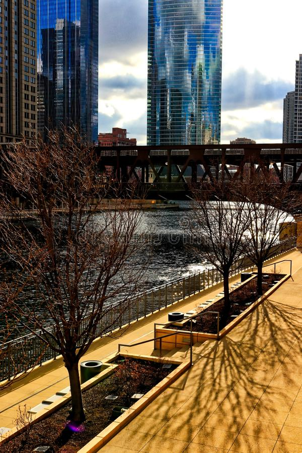 Shadows of trees fan across the sidewalk along the Chicago River as the sun turns from winter to spring at sunset. stock image