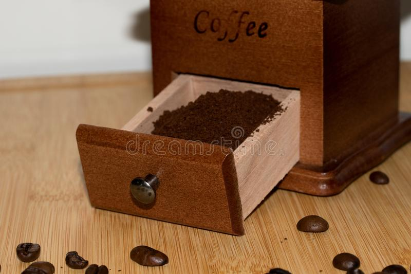 A drawer of a coffee mill with coffee powder and some coffee beans royalty free stock photo