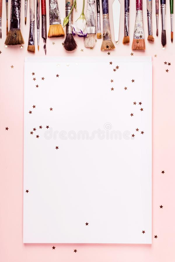 Drawing album frame, row brush and golden stars on pink background stock photo