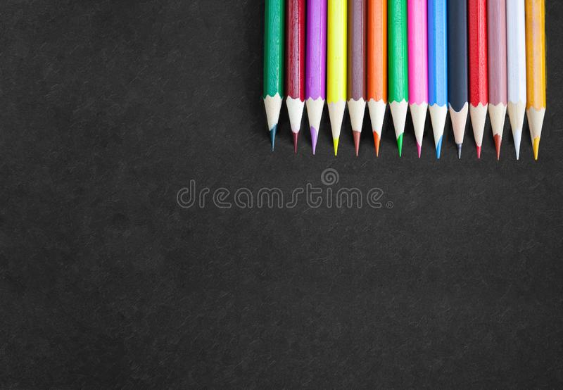 Drawing banner concept, Colorful pencils on top right corner on black canvas with textured. Art drawing banner poster concept, Colorful crayon pencils in a row royalty free stock photos