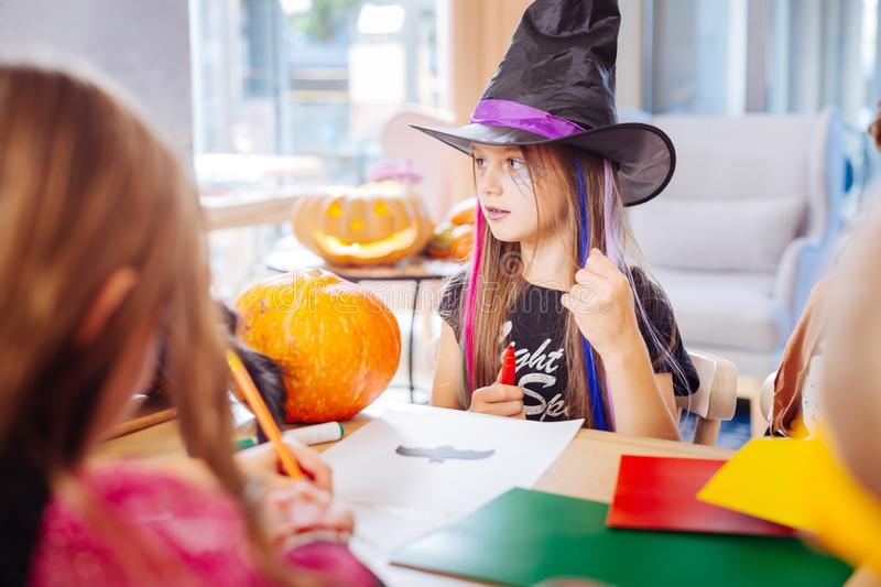 Beautiful girl wearing black wizard hat for Halloween drawing little black bat. Drawing bat. Beautiful dark-haired girl with purple lips wearing black wizard hat royalty free stock images