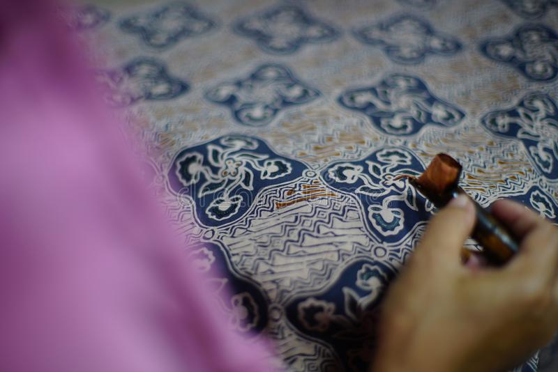 Drawing Batik Tulis on the fabric. Close Up hand to make batik with canting on fabric royalty free stock photo