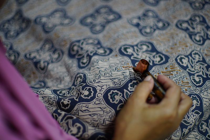 Drawing Batik Tulis on the fabric. Close Up hand to make batik with canting on fabric royalty free stock photography
