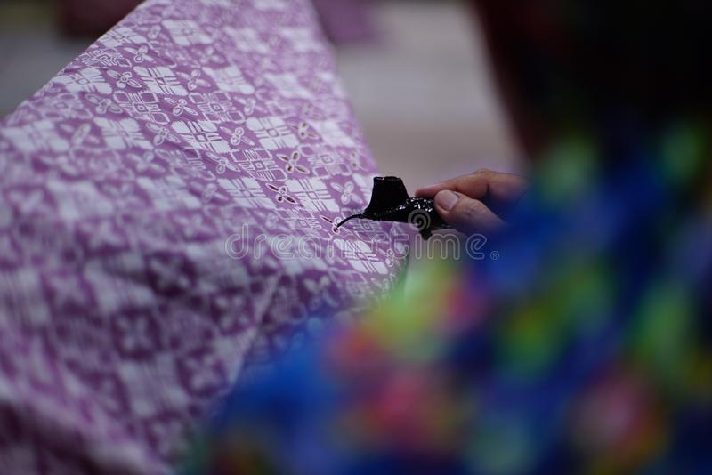 Drawing Batik Tulis on the fabric. Close Up hand to make batik with canting on the purple colour fabric royalty free stock photo