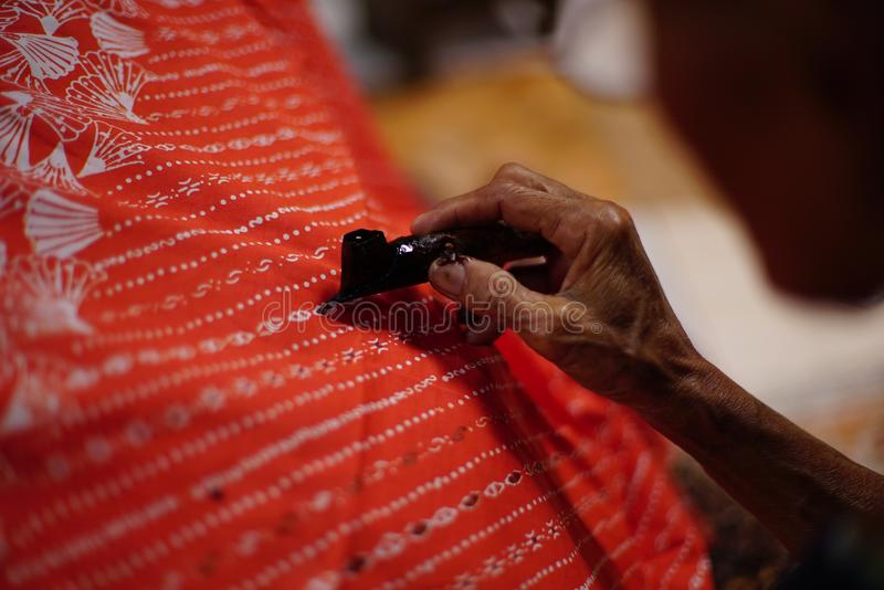 Drawing Batik Tulis on the fabric. Close Up hand to make batik with canting on the red colour fabric stock image