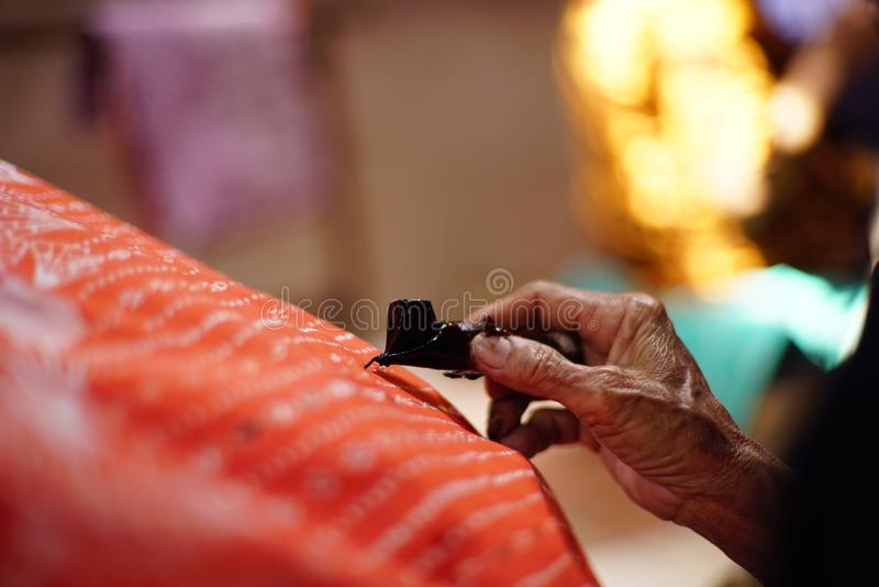 Drawing Batik Tulis on the fabric. Close Up hand to make batik with canting on the red colour fabric stock photo