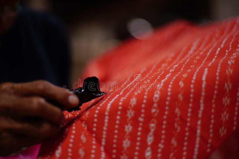 Drawing Batik Tulis on the fabric. Close Up hand to make batik with canting on the red colour fabric stock photos