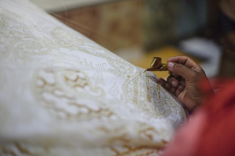Drawing Batik Tulis on the fabric. Close Up hand to make batik with canting on fabric. Traditioinal Culture Indonesia royalty free stock photo