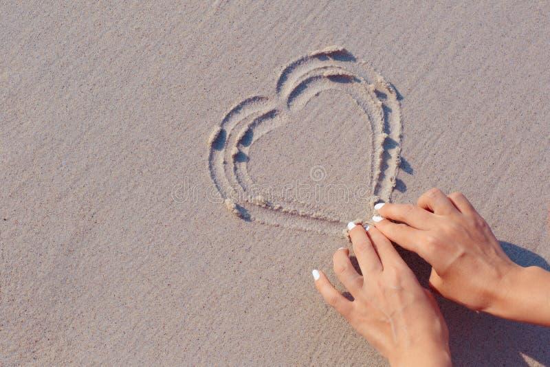 Drawing on beach sand heart symbol stock image