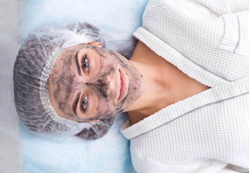 Drawing a black mask. Drawing a black mask on the patient`s face. Beauty saloon royalty free stock photography