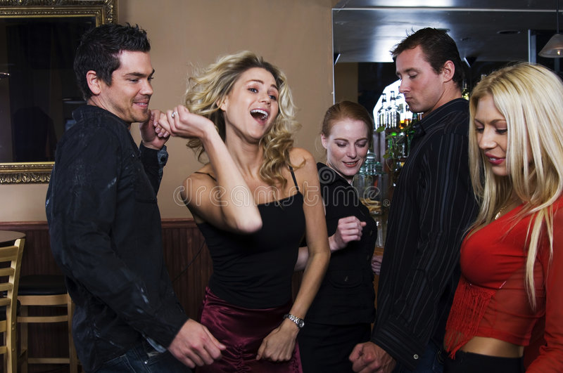 Drawing the crowd. Young woman dances in a ludicrous manner under the lusty looks of her audience, at a party in a pub
