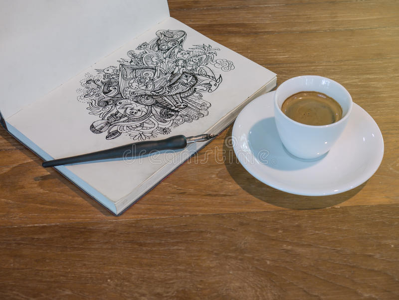Drawing Doodle line art by black ink on paper with a cup of coffee. Closeup drawing doodle line art by black ink on paper with a cup of coffee royalty free stock photos