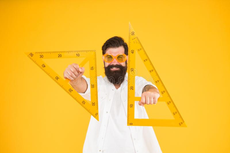 For drawing, draughting and design. Hipster holding drawing instruments on yellow background. Architect and engineer royalty free stock images
