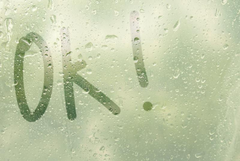 Drawing a finger-shaped stripe of the word ok on the translucent soaked glass. raindrops of spring rain on the window close-up. Blurred background copy space stock image