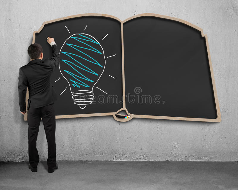 Drawing glowing lamp on book shape blackboard. Businessman standing and drawing glowing lamp on book shape blackboard stock photos