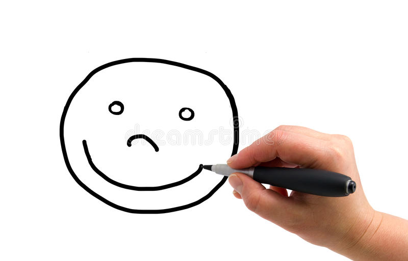 Drawing happy face. Illustration of the hand with a pen drawing smiling face on the white paper background stock photos