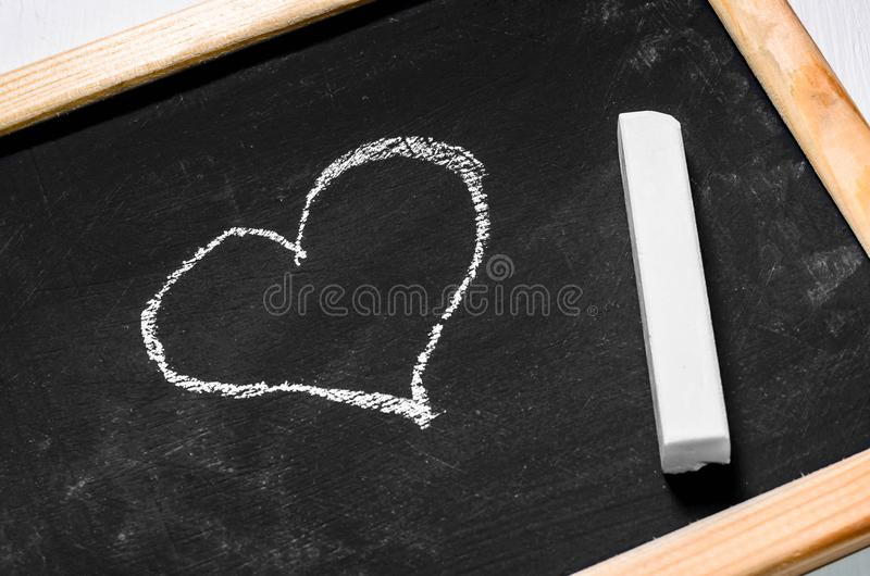 Drawing heart on a chalkboard. Top view royalty free stock photos