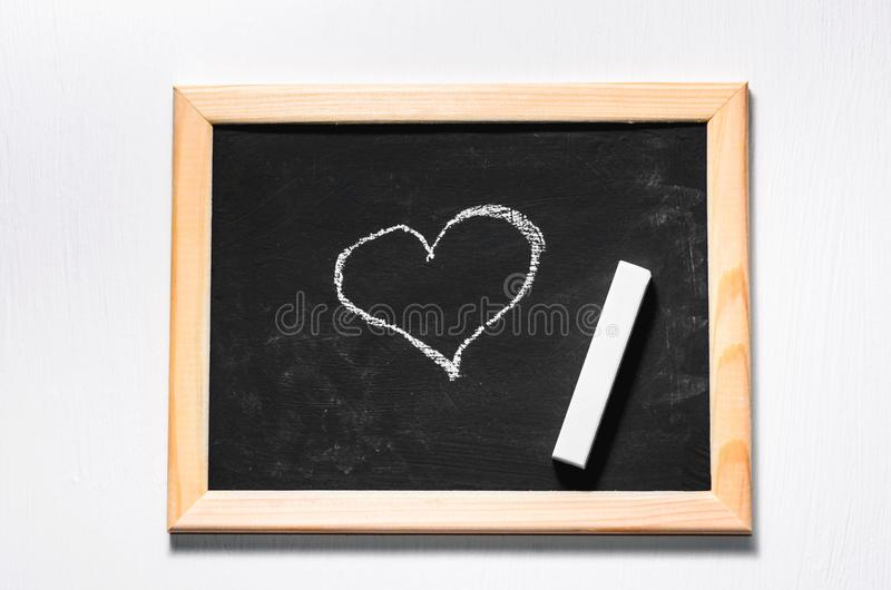Drawing heart. On a chalkboard royalty free stock photography