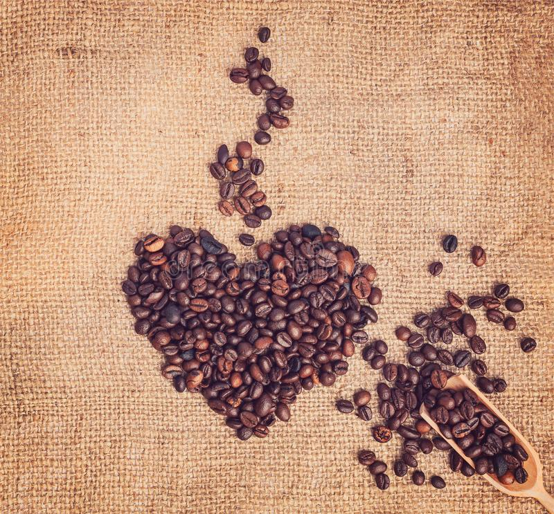 Drawing heart with fragrant steam from coffee beans on sackcloth background. Nearby is a wooden spoon. Vintage style. stock photos