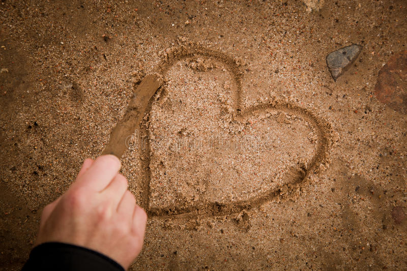 Drawing heart on ground. Close up of a hand drawing a heart shape on ground stock photography