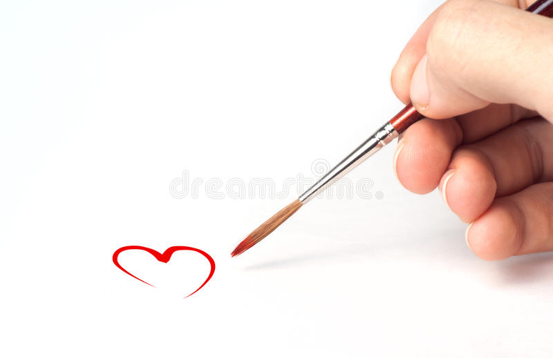 Drawing heart. Harvesting of Valentine's Day. Brush in the arm Drawing heart. Harvesting of Valentine's Day stock photo