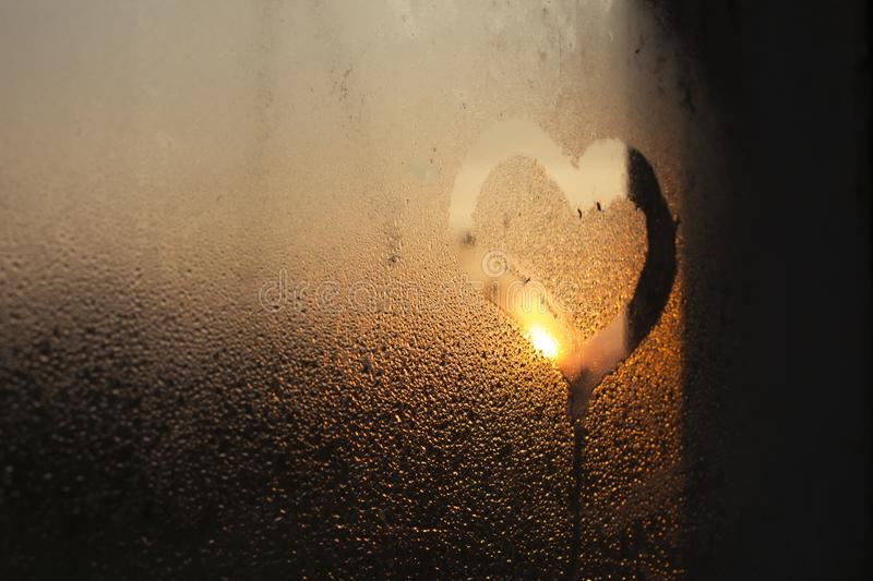 A drawing of a heart on a misted glass window against a sunset / dawn. Morning. Evening. Sunset. Sunrise royalty free stock photography