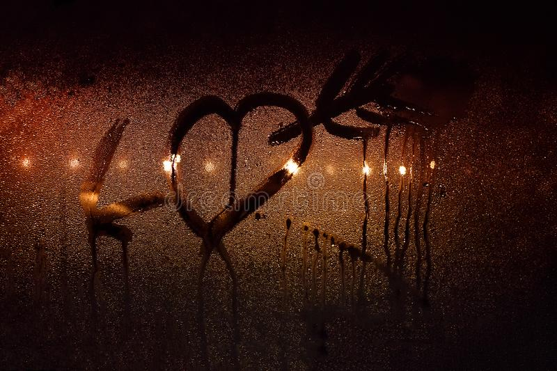 A drawing of a heart pierced by Cupid`s arrow on the sweaty glass of the car in backlit city lights stock image