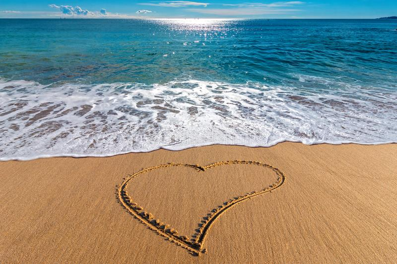 Drawing heart on the sand in the beach royalty free stock image