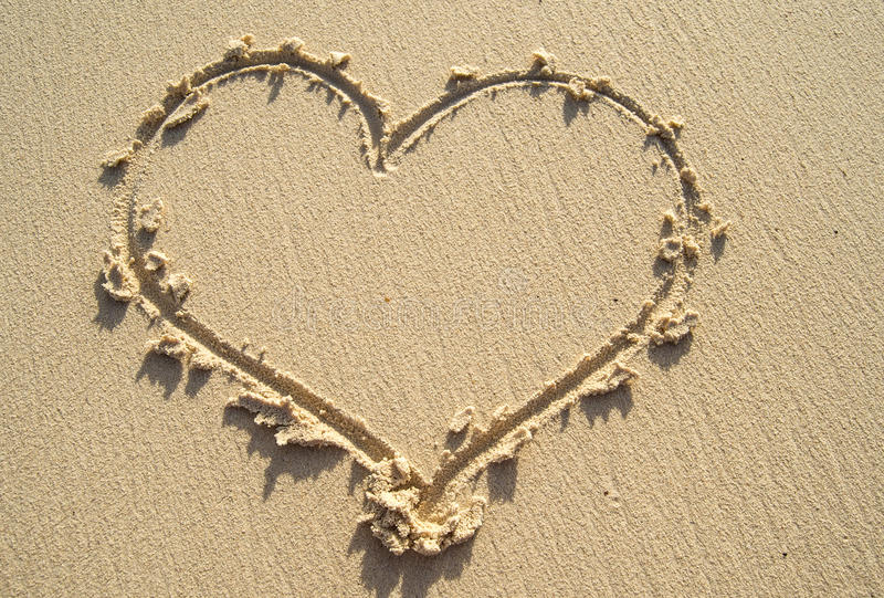 Drawing heart on sand beach. Heart symbol on sand stock images