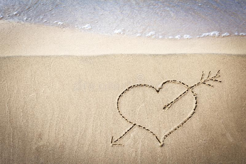 A drawing of a heart on a sand at seascape background. royalty free stock images