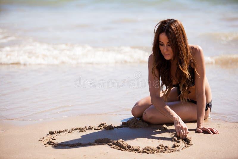 Drawing a heart in the sand. Girl in bikini drawing a heart in the sand with her hand stock images
