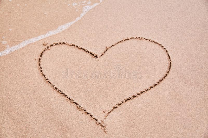 Drawing a heart on the sand. Sign of love stock photography
